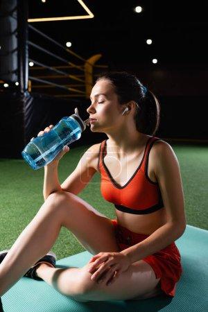 Photo pour Sportif assoiffé avec écouteur boire de l'eau de la bouteille de sport tout en étant assis sur tapis de fitness avec les yeux fermés - image libre de droit