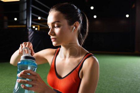 thirsty sportswoman with earphone opening sports bottle in gym