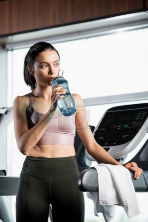 Photo for Thirsty sportswoman standing on treadmill and drinking from sports bottle - Royalty Free Image