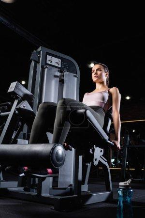 Photo pour Sportive sportive faisant l'exercice d'extension de jambe sur la machine d'entraînement - image libre de droit