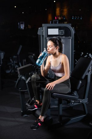 junge Sportlerin sitzt mit geschlossenen Augen auf Trainingsgerät und trinkt aus Sportflasche