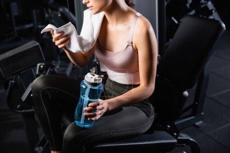 Foto de Vista parcial de la deportista sosteniendo la toalla y la botella de deporte mientras está sentada en la máquina de entrenamiento - Imagen libre de derechos