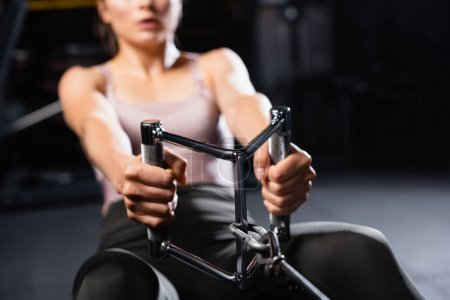 partial view of sportswoman training on rowing machine in sports center on blurred background