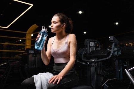 Photo pour Sportive fatiguée assise sur une machine d'entraînement les yeux fermés et tenant une bouteille de sport - image libre de droit