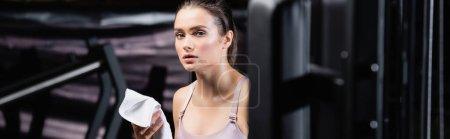 Photo pour Jeune sportive regardant la caméra tout en tenant une serviette dans la salle de gym, bannière - image libre de droit