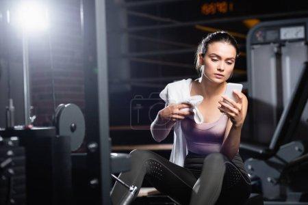 Sportlerin sitzt auf Trainingsgerät und nutzt Smartphone im Fitnessstudio im unscharfen Vordergrund