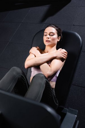 Photo for High angle view of athletic sportswoman with crossed arms exercising on leg press machine on blurred foreground - Royalty Free Image