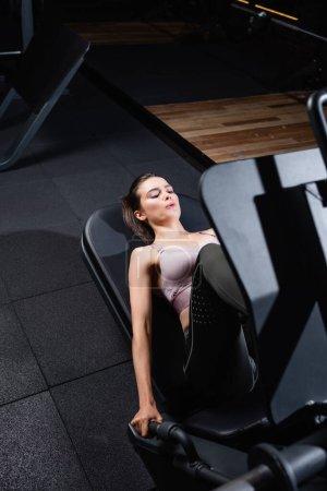 Photo pour Vue à angle élevé d'une sportive travaillant sur une presse à jambes faisant de l'exercice sur un premier plan flou - image libre de droit
