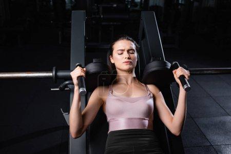 Photo pour Vue grand angle de la femme sportive en soutien-gorge de sport entraînement sur bras machine d'extension avec les yeux fermés - image libre de droit