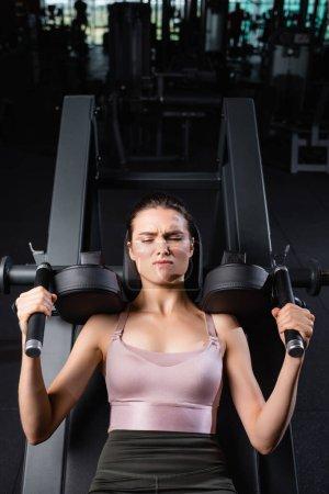 Photo pour Vue de dessus de la sportive avec les yeux fermés formation sur la machine d'extension des bras dans la salle de gym - image libre de droit