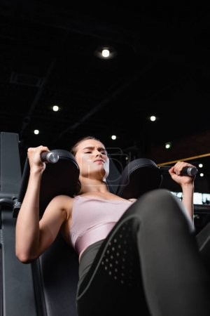 Photo for Athletic sportswoman doing arms extension exercise on training machine on blurred foreground - Royalty Free Image
