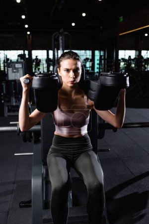 sportswoman in top and leggings working out on arms extension exercising machine
