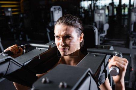 Photo pour Sportive tendue travaillant sur la machine d'extension des bras dans la salle de gym - image libre de droit