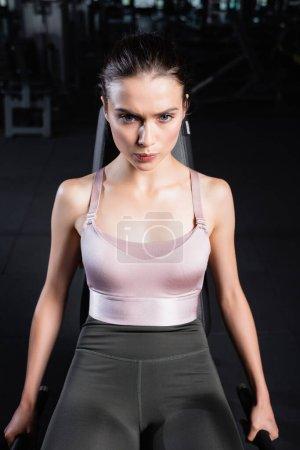 Photo pour Tendue sportive en haut et leggings formation sur la machine d'exercice dans la salle de gym - image libre de droit