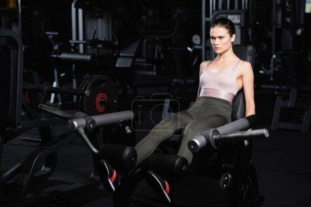 Photo pour Sportive concentrée faisant l'exercice d'extension de jambe sur la machine d'entraînement - image libre de droit