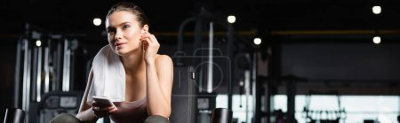 sportswoman smiling while holding cellphone and listening music in wireless earphone in gym, banner