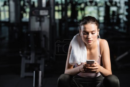 sportswoman messaging on cellphone while sitting in gym with towel on shoulder
