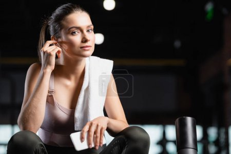sportswoman looking at camera while holding smartphone and listening music in wireless earphone in sports center