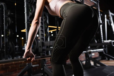 cropped view of sportswoman working out with power rack in sports center
