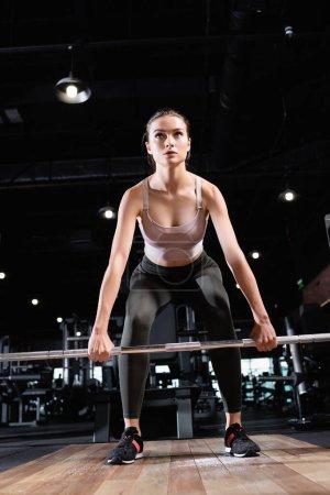Photo pour Femme athlétique faisant de l'exercice avec support de puissance dans le centre sportif - image libre de droit