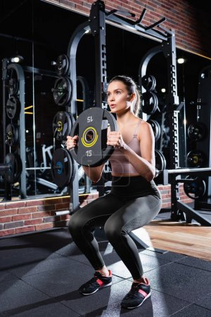 athletic sportswoman in leggings doing sit ups with weight disk in gym