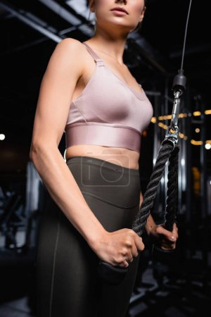 partial view of sportive woman in sports bra and legging working out on triceps extension machine