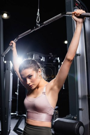 Photo for Sportive woman in sports bra looking at camera while training on lat machine - Royalty Free Image