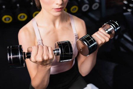 Photo for Cropped view of sportswoman working out with dumbbells in sports center - Royalty Free Image