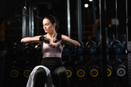 young sportswoman sitting and training with dumbbells in sports center