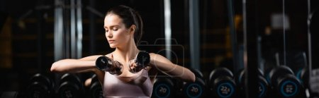 young sportswoman sitting and working out with dumbbells in gym, banner