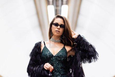 stylish woman in black lurex dress and sunglasses holding wine bottle at underground station