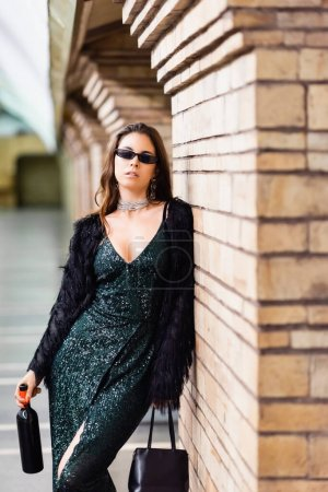 seductive woman in black lurex dress and sunglasses standing with wine bottle near brick column at metro station