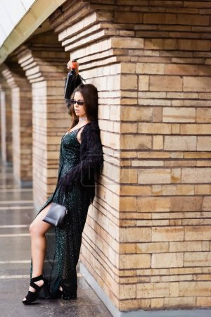 seductive woman in long black dress leaning on brick column while holding wine bottle in raised hand
