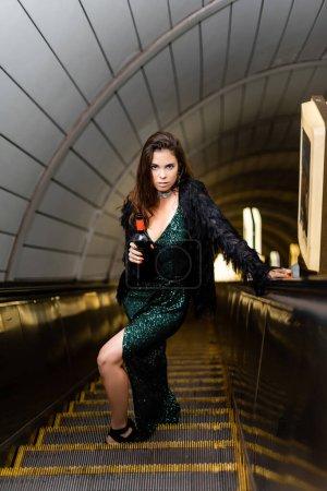Photo pour Femme séduisante en robe de lurex noir avec bouteille de vin regardant la caméra sur l'escalator du métro - image libre de droit