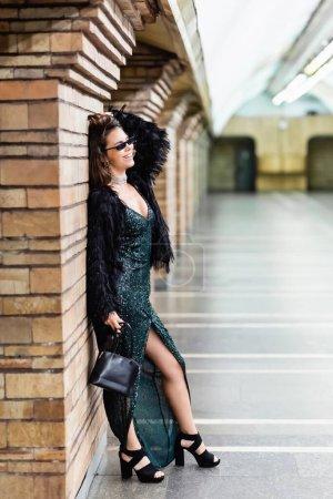 Photo pour Heureuse femme glamour en robe noire longue posant près colonne de brique à la station de métro - image libre de droit