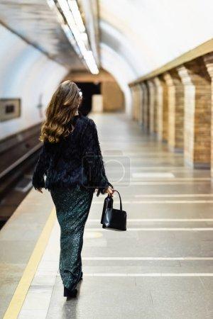 back view of stylish woman in long lurex dress walking along metro platform