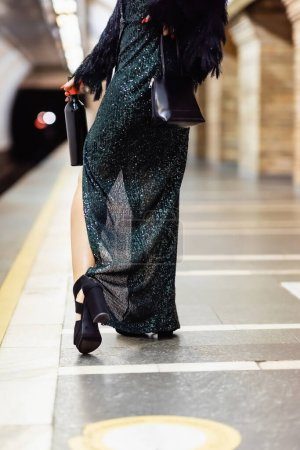 Photo for Cropped view of stylish woman in long black dress holding bottle of wine on metro platform - Royalty Free Image