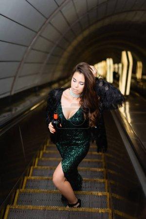 Photo pour Femme séduisante en robe noire élégante touchant les cheveux tout en tenant la bouteille de vin sur l'escalator - image libre de droit