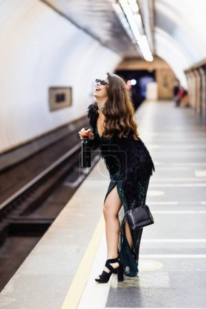 glamour woman in black lurex dress and sunglasses laughing while holding wine bottle on metro platform