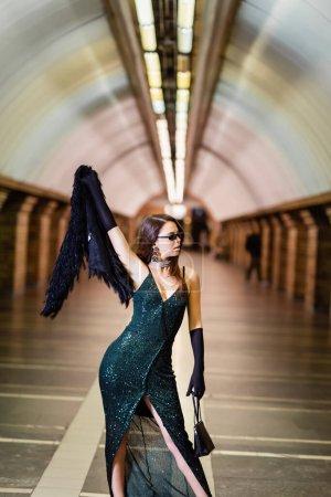 Photo pour Femme sensuelle en robe lurex noire posant avec une veste en fausse fourrure à la station de métro - image libre de droit