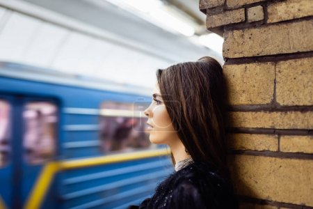 young woman looking at blurred train while standing on platform near brick column