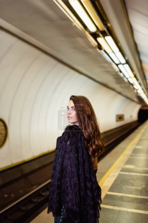 glamour woman in faux fur jacket looking at camera while standing on subway platform