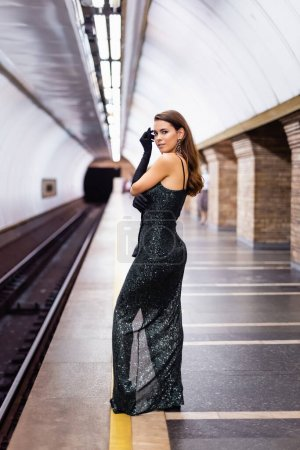 sensual woman in long black dress looking at camera while standing on underground platform