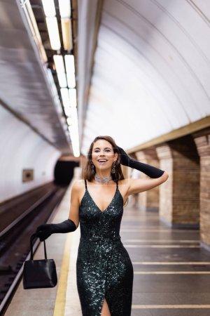 cheerful woman in black lurex dress smiling at camera on underground platform