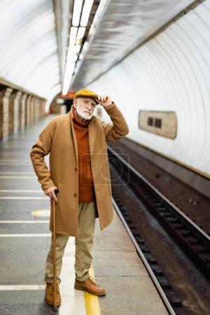 senior man in autumn outfit touching cap while standing on metro station platform