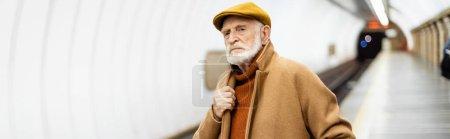 senior man touching collar of coat while standing on metro platform, banner