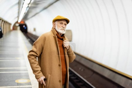 senior man in autumn outfit touching collar of coat while looking away on metro platform