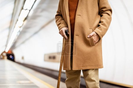 cropped view of aged man with walking stick, wearing autumn coat, standing on metro platform