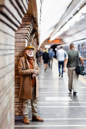 aged man in autumn outfit standing near people and train on metro platform on blurred foreground