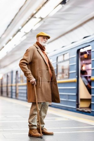 elderly man in cap and coat standing on metro station platform near train on blurred background